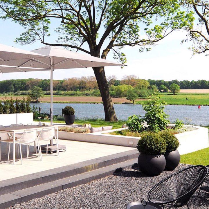 De tuin voor de gasten met loungehoek, eettafel met witte stoelen en zicht op de Maas