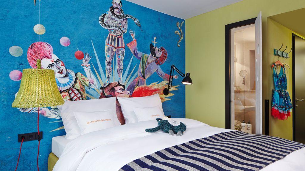 Kleurrijke slaapkamer met muurschildering en zwartwitte sprei op bed