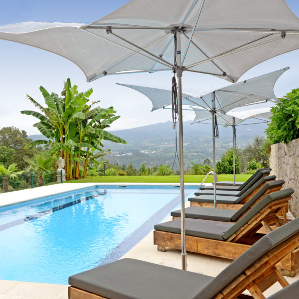 Zwembad met ligstoelen en witte parasols