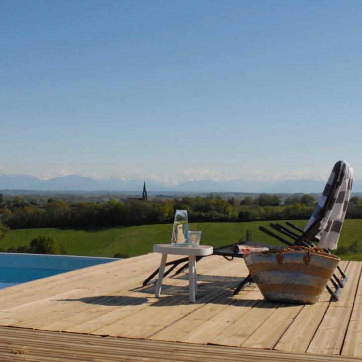 Zwembad met ligstoelen, wit tafeltje en rieten mand