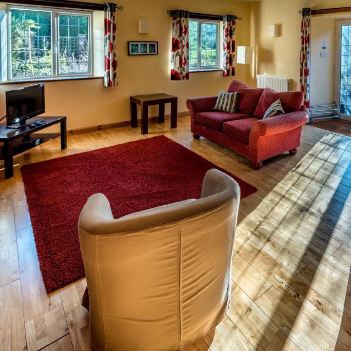Een rode bank en bruine stoel rond een rood tapijt