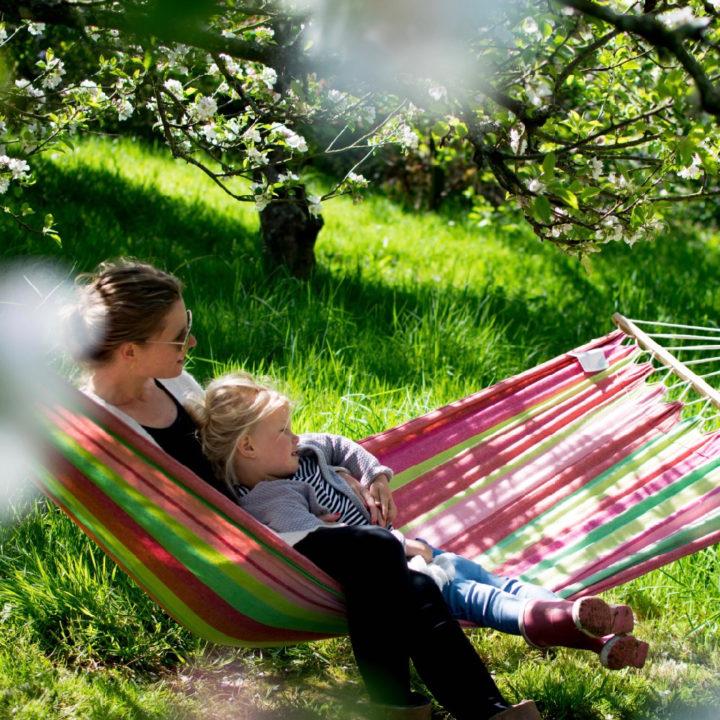 Een moeder zit met haar kind in een gekleurde hangmat