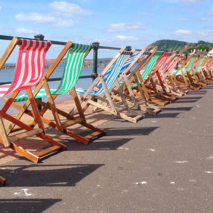 Verschillende strandstoelen met gestreepte patronen staan naast elkaar