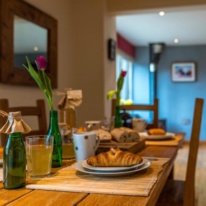 Een gedekte eettafel met croissantjes op de borden
