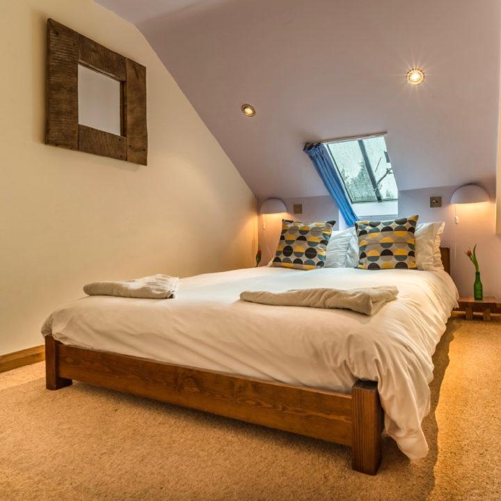 Opgemaakt bed onder het licht van een dakraam