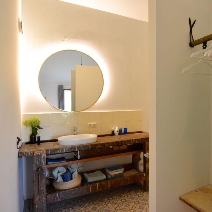 Open badkamer met oude werkbank als wastafel blad