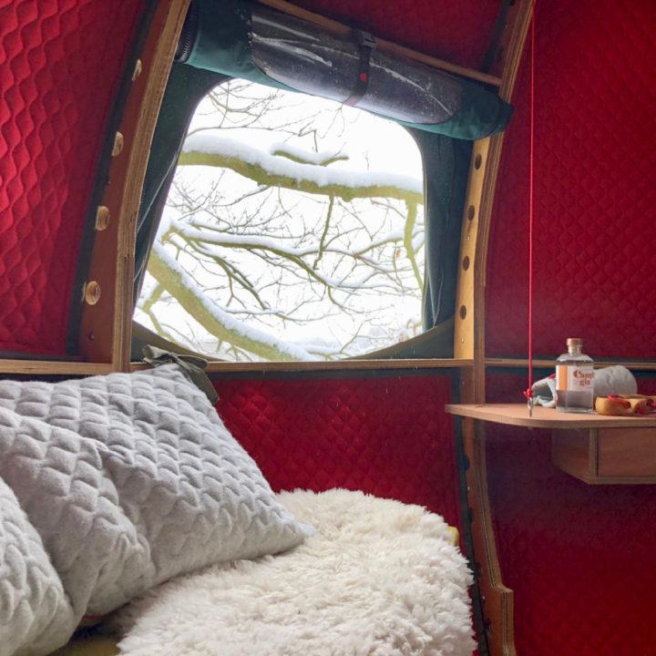 Rode boomhut met bankje er in witte kussens en een vachtje