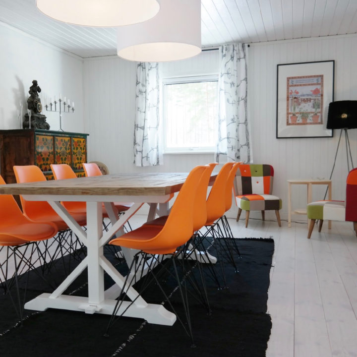 Witte houten eettafel met oranje stoelen
