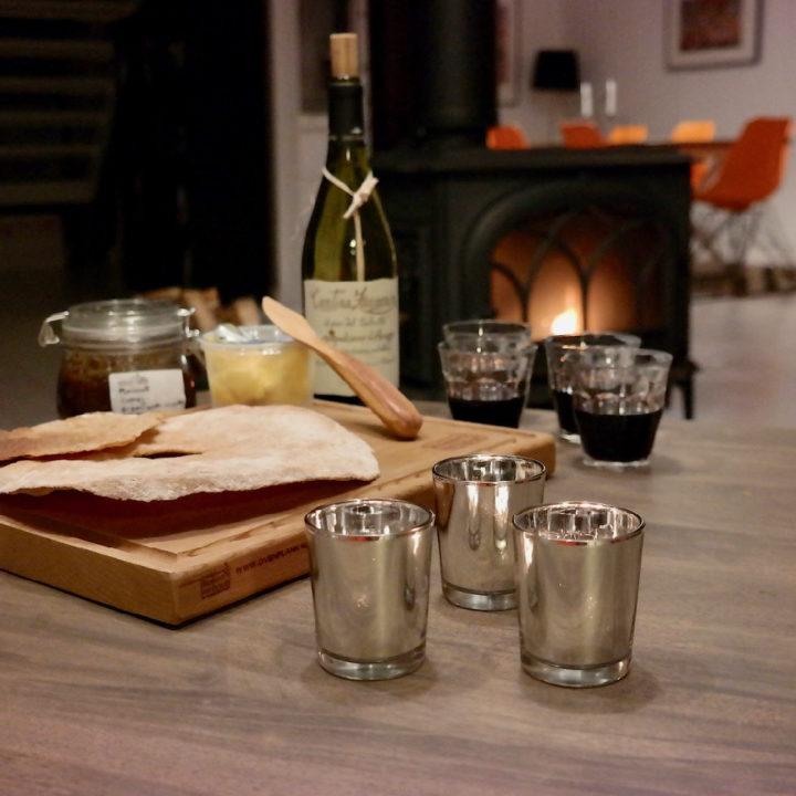 Tafel met plank met lekkers en wijnfles met wijnglazen voor brandende kachel