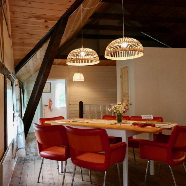Eettafel met twee lampen erboven en rode stoelen eromheen