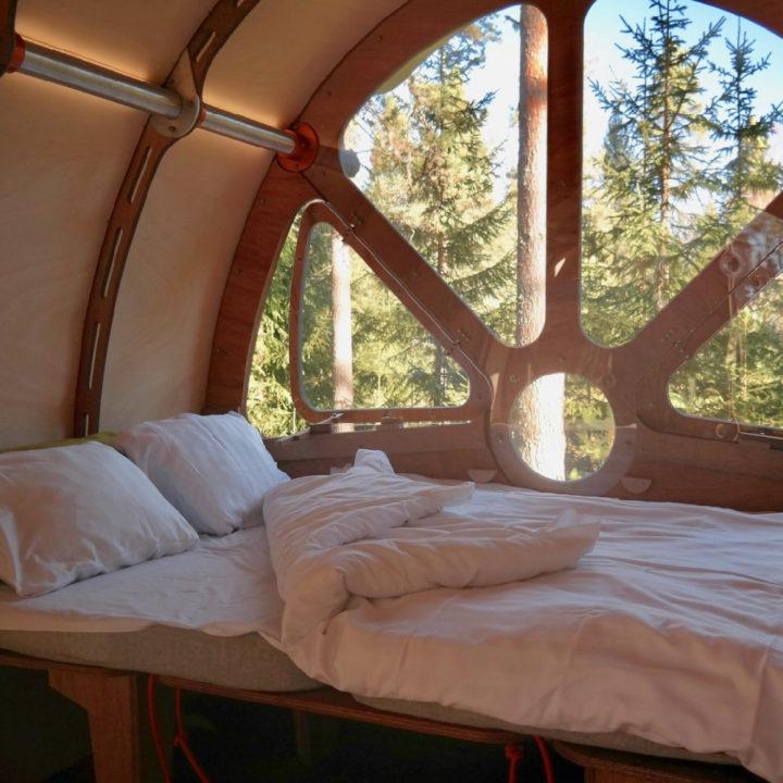 Opgemaakt bed met witte dekbedden, voor een raam met zicht op groen