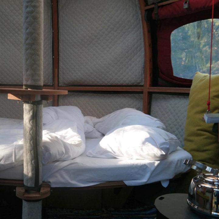 Een opgemaakt tweepersoons bed met een geel kussen, in een ronde boomhut