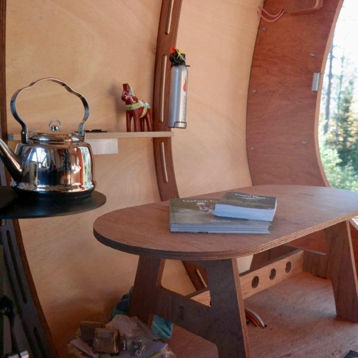 Houten ronde eettafel met boeken er op en fluitketel