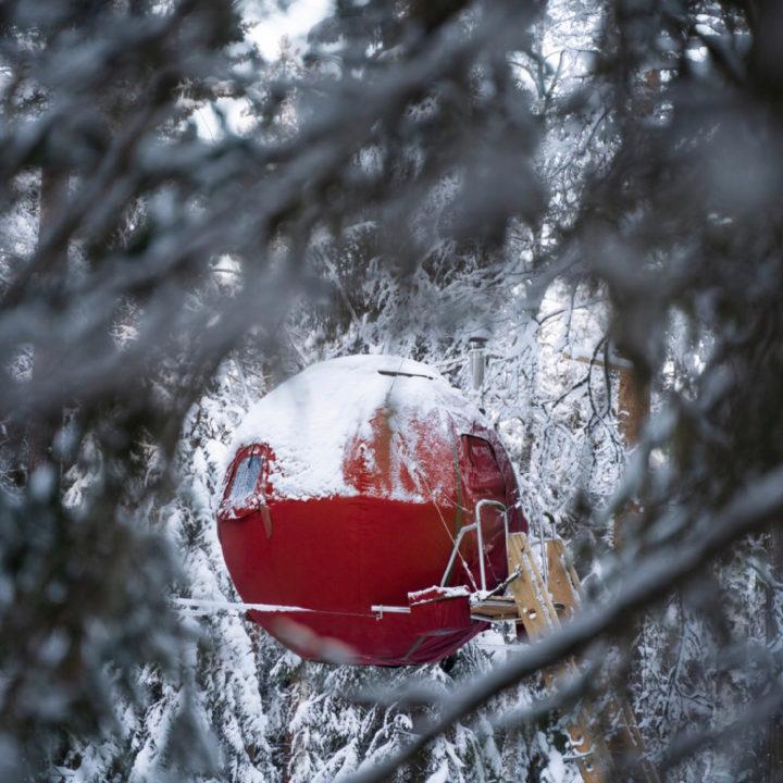 Rode ronde boomhut in de sneeuw