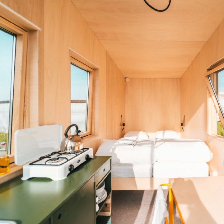 Tweepersoons bed in een houten tiny house