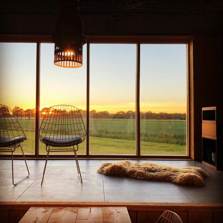Duurzaam vakantiehuis met grote ramen en twee stoelen voor het raam