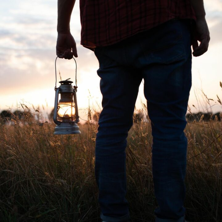 Man met olielamp voor de zonsondergang