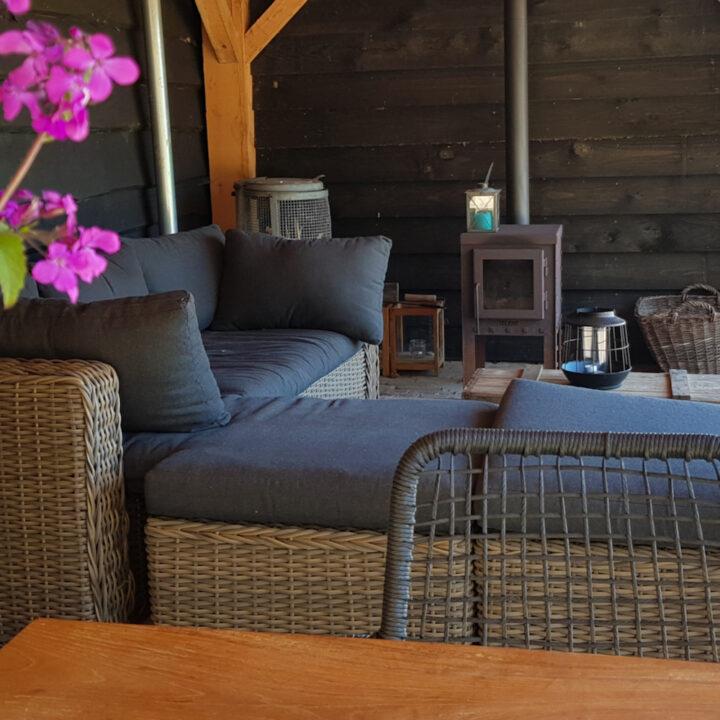 Veranda met houtkachel en loungebanken bij het vakantiehuis
