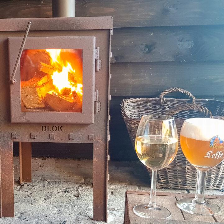 Brandende houtkachel met biertje en wijntje bij het vakantiehuis