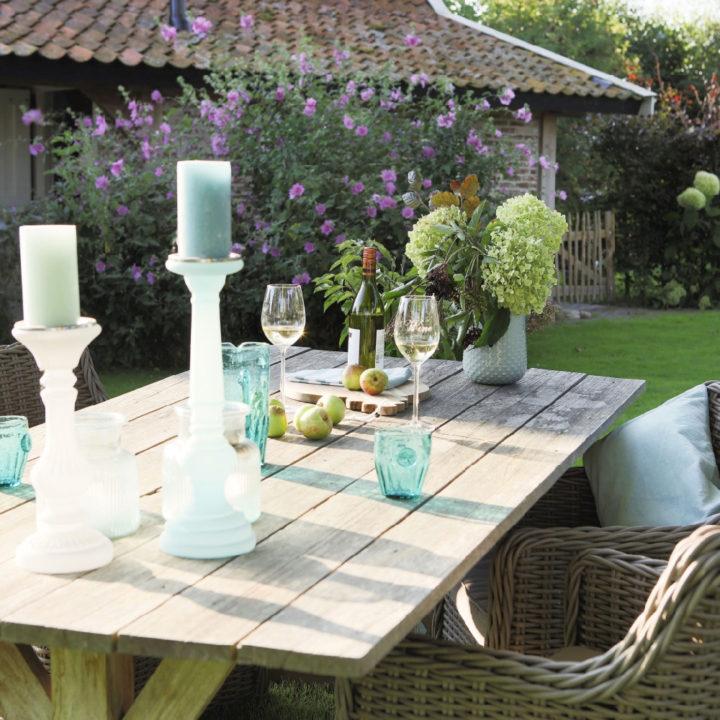 Gedekte tafel in de tuin, met kaarsen en glazen