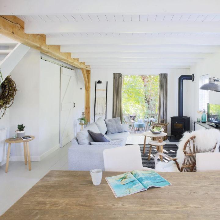 Woonkamer met veel wit, houten balken, een lichtgrijs bankstel
