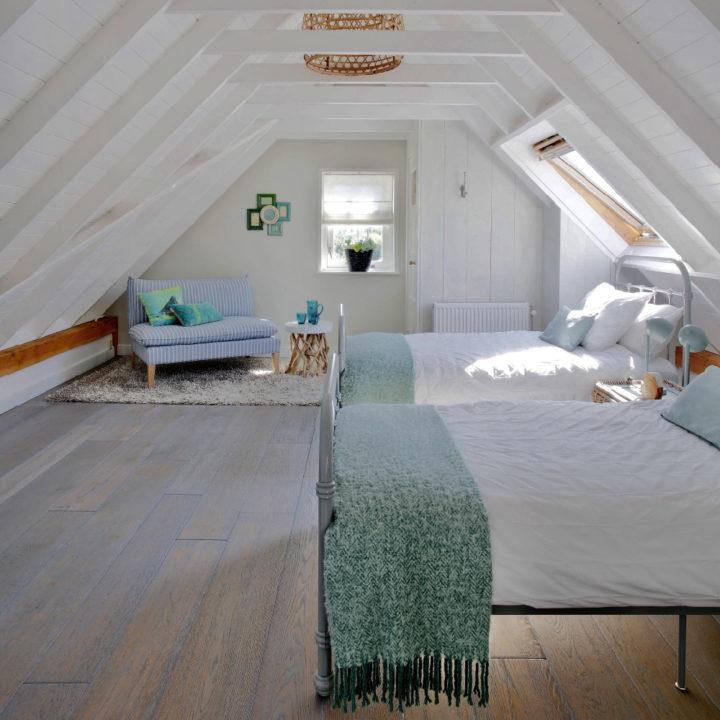 Slaapkamer met schuine daken en twee spijlenbedden met wit beddengoed