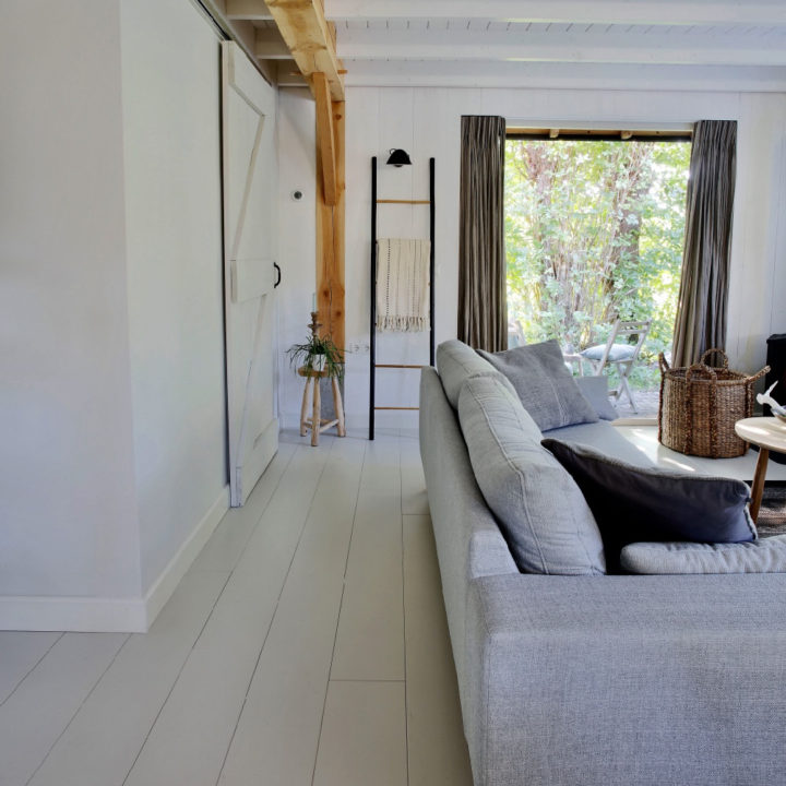 Grijze zitbank in woonkamer, openslaande tuindeur