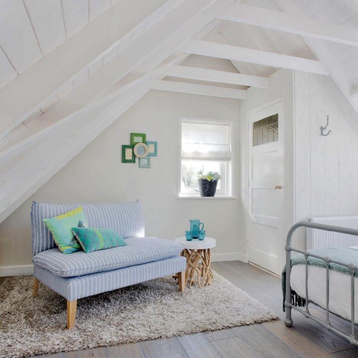 Een kleine zitbank in lichtgrijs op slaapkamer
