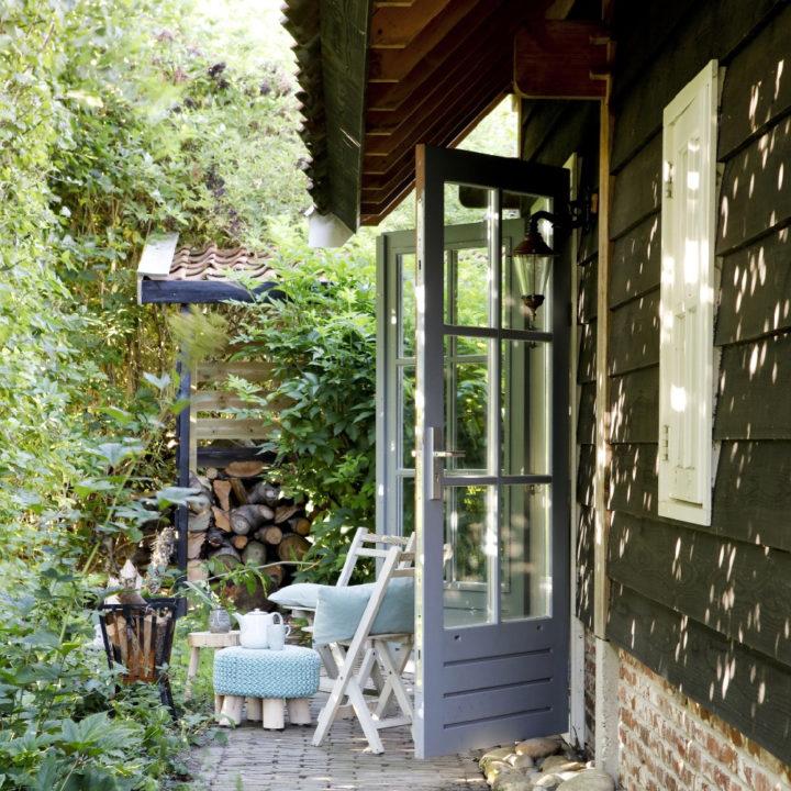 Openslaande tuindeuren met daarvoor een zitje met kussens, een plaid en kleine poef