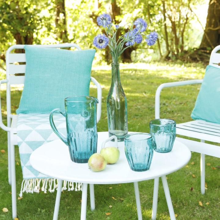 Zitje met witte stoelen en wit tafeltje, met azuurblauwe accessoires