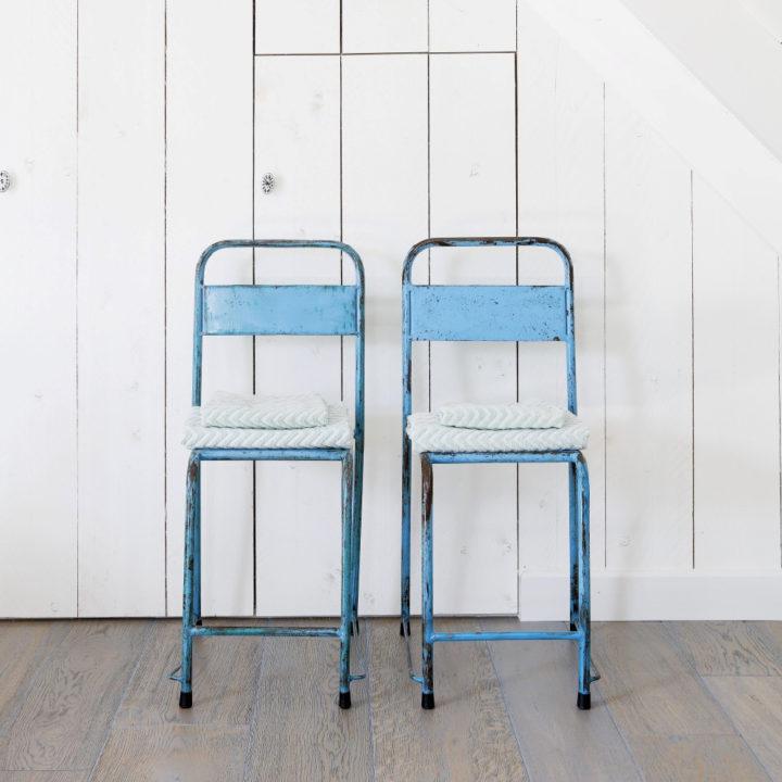 Twee metalen hoge stoelen in blauw, tegen witte muur