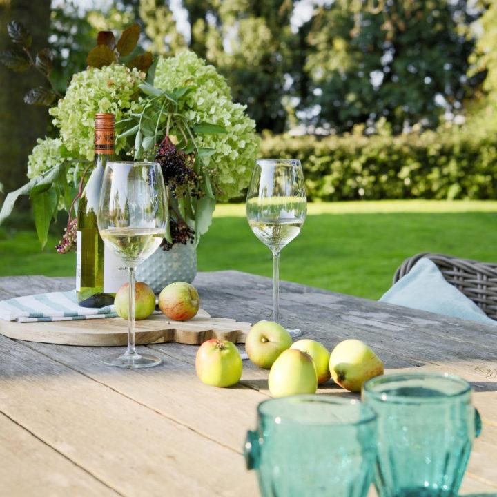 Houten eettafel met blauwe glazen, appels en wijnglazen