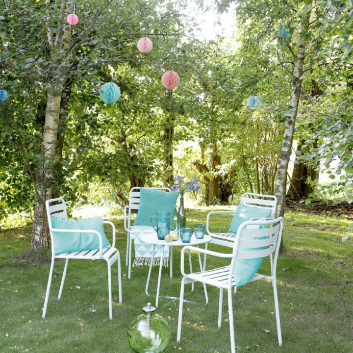 Genieten in de tuin, witte stoeltjes, blauwe kussens en roze lampionnen