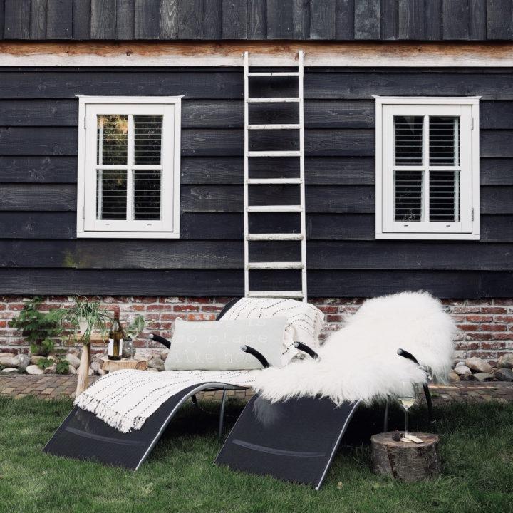 Twee ligstoelen met bontjes erop, voor een zwarte houten gevel met een trappetje