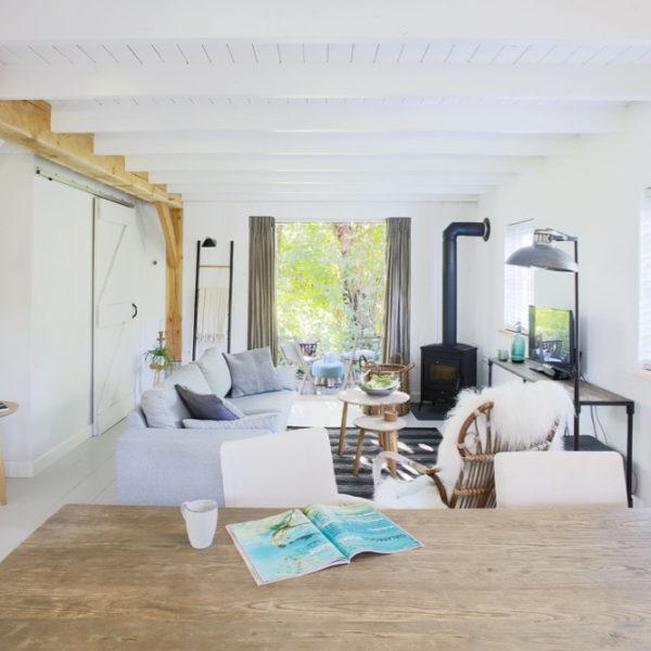 Licht woonkamer met eettafel en grijze zitbank bij een zwarte houtkachel, openslaande deuren