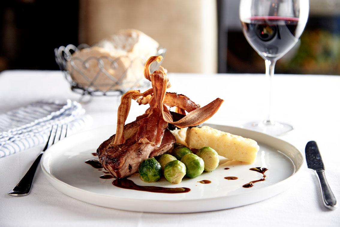 Prachtig opgemaakt bord met groente, vlees en aardappelen, glas rode wijn ernaast