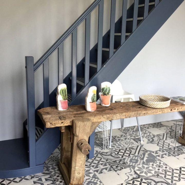 Open blauwe houten trap naar boven met tafeltje ernaast & kinderstoel er onder