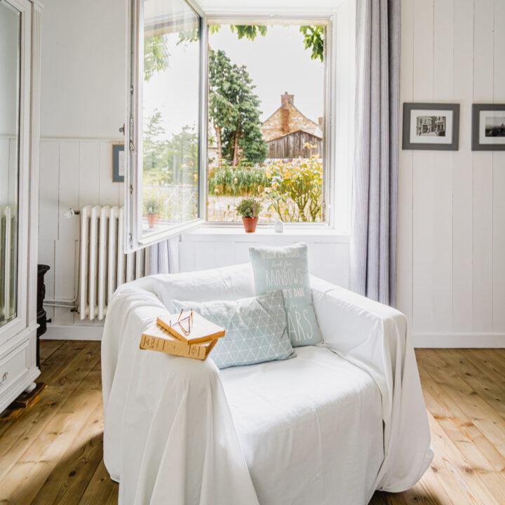 Witte fauteuils met mintkleurige kussens voor een open raam