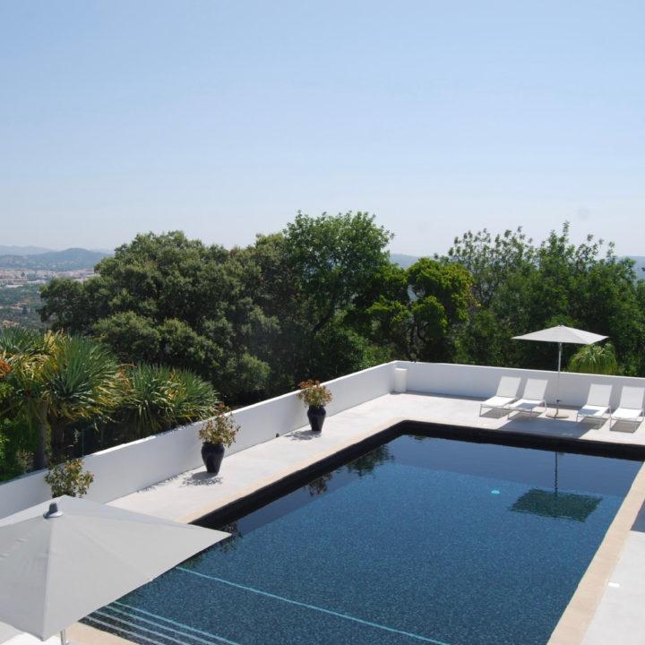 Zwembad van zwart mozaïek met witte ligstoelen en parasol