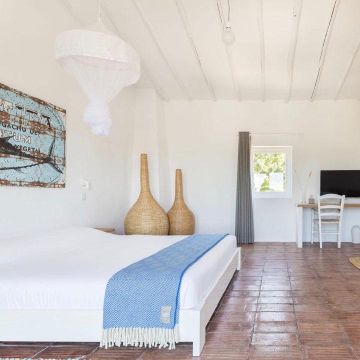 Slaapkamer met wit bed, terracotta tegels en witte muren