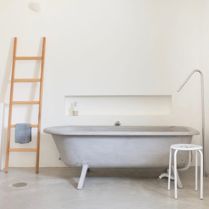 Grijs bad op pootjes, houten trapje met handdoek ernaast