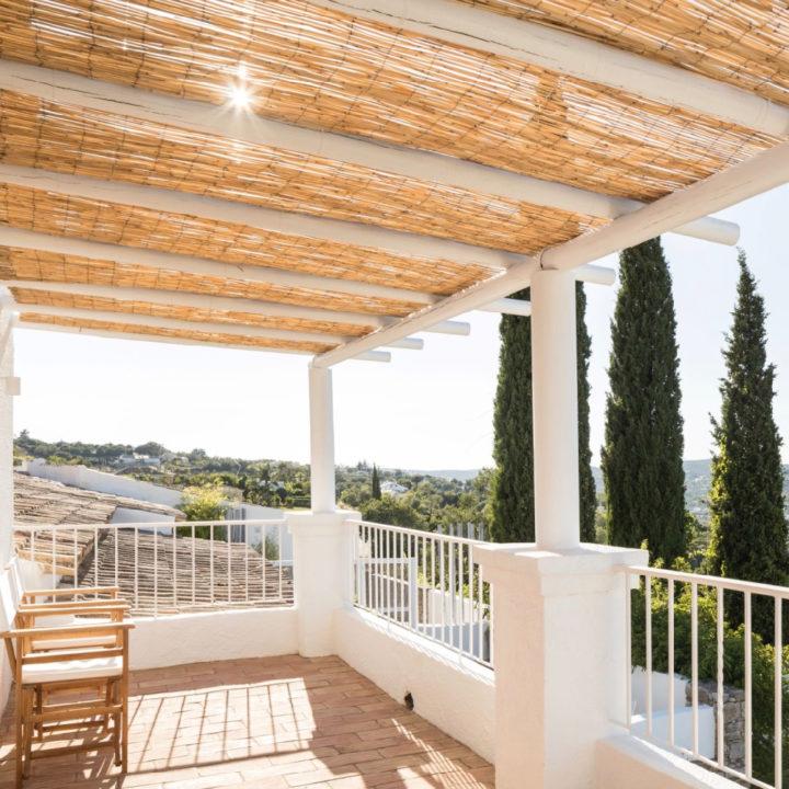 Overdekt balkon met twee regisseurstoelen, een rieten dak en zonnestralen