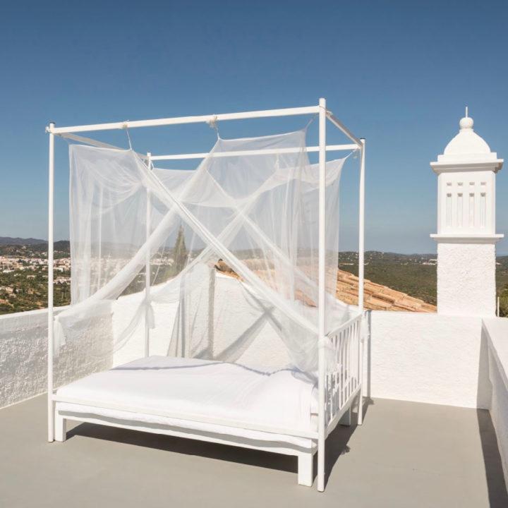 Wit hemelbed op dak van een bed and breakfast, slapen in de open lucht