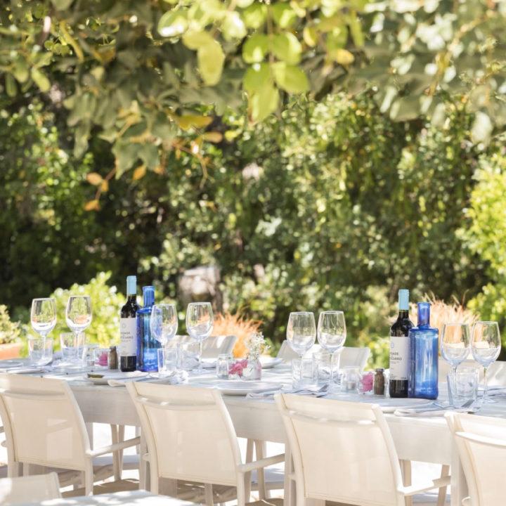 Gedekte witte tafel met glazen en flessen wijn, in de buitenlucht