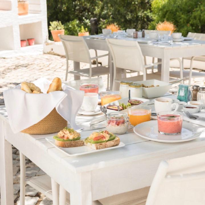 Witte tafels in de schaduw met ontbijt erop