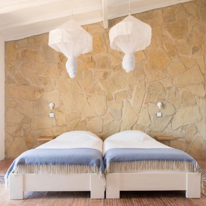 Twee losse bedden met witte klamboe erboven en lichtgrijze sprei