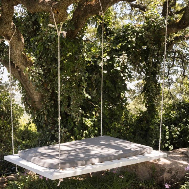 Een bed met grijs matras hangend aan een boom
