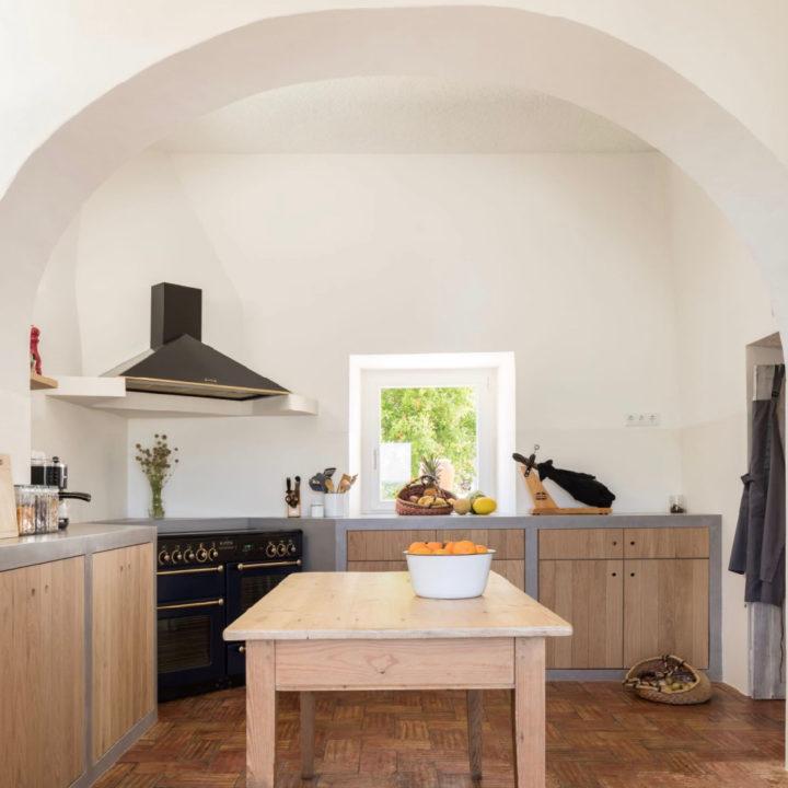 Houten keuken met betonnen aanrecht, witte muren en tafel met schaal sinaasappels