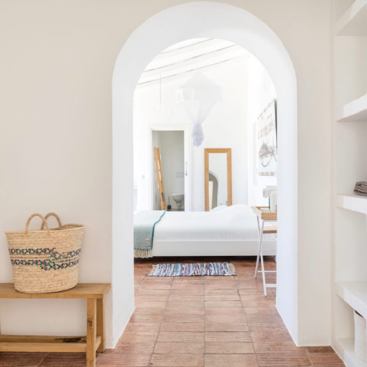Witte muren, terracotta tegelvloer en doorkijkje naar tweepersoons bed