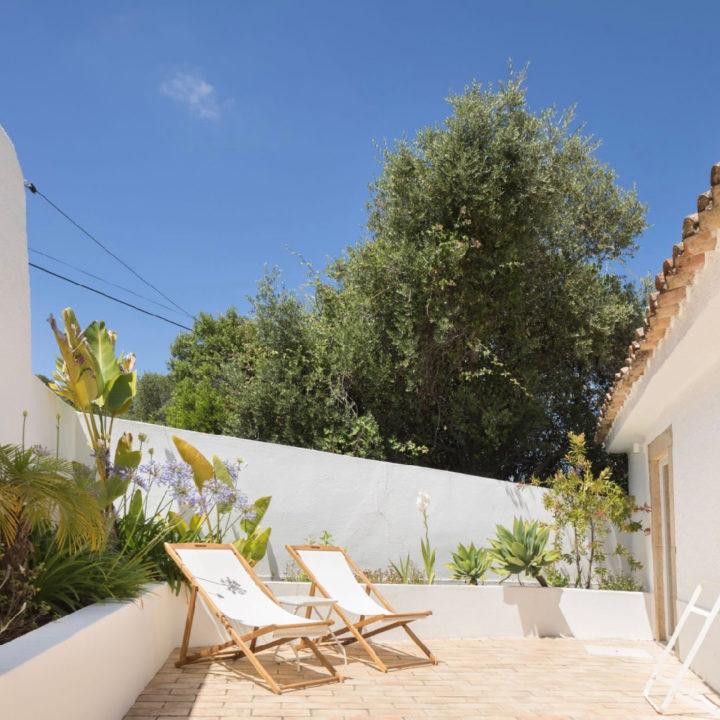 Terras met twee witte strandstoelen en witte muren
